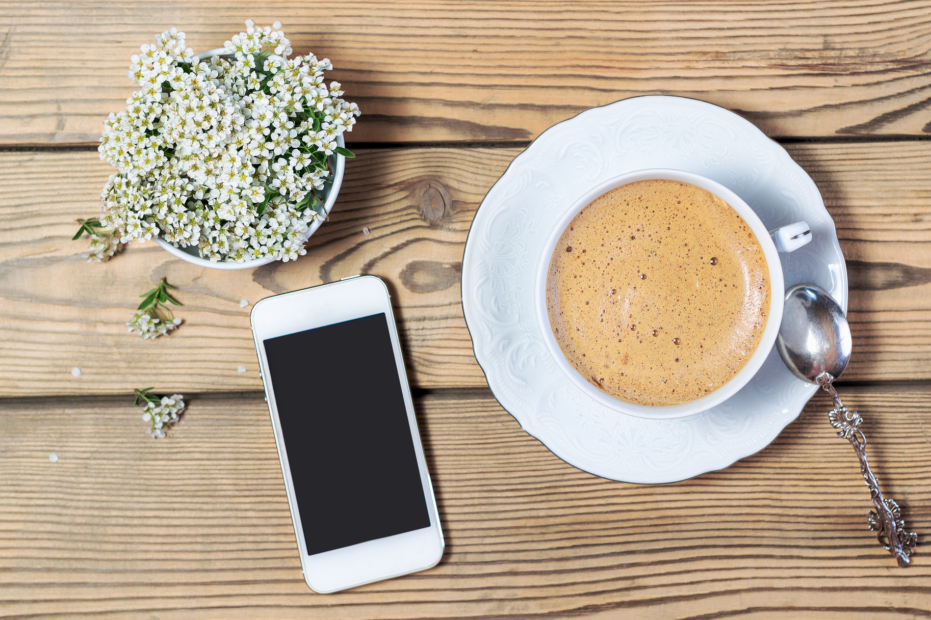 Cup of coffee, mobile phone and flowers on wooden table